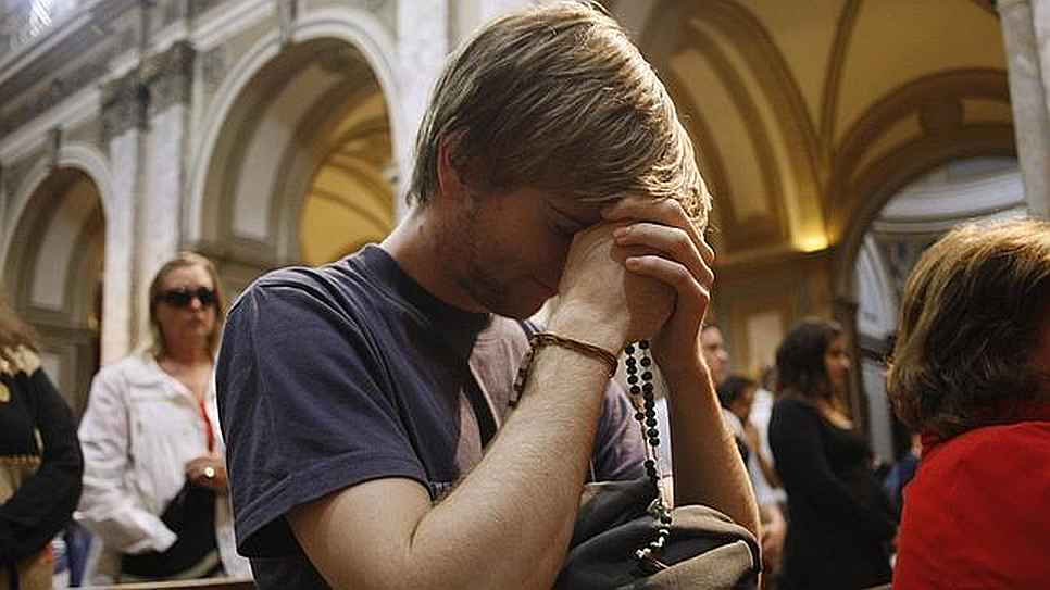 joven rezando iglesia