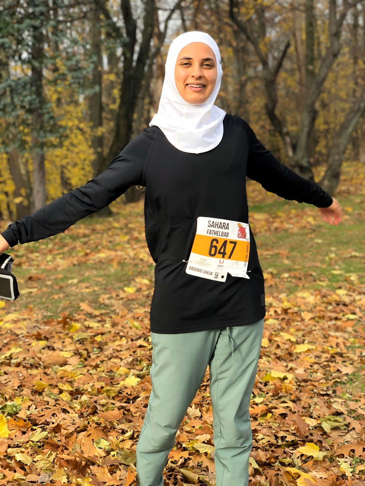 sahara with white nike hijab, black nike long sleeve and green running pants with wind blowing behind her