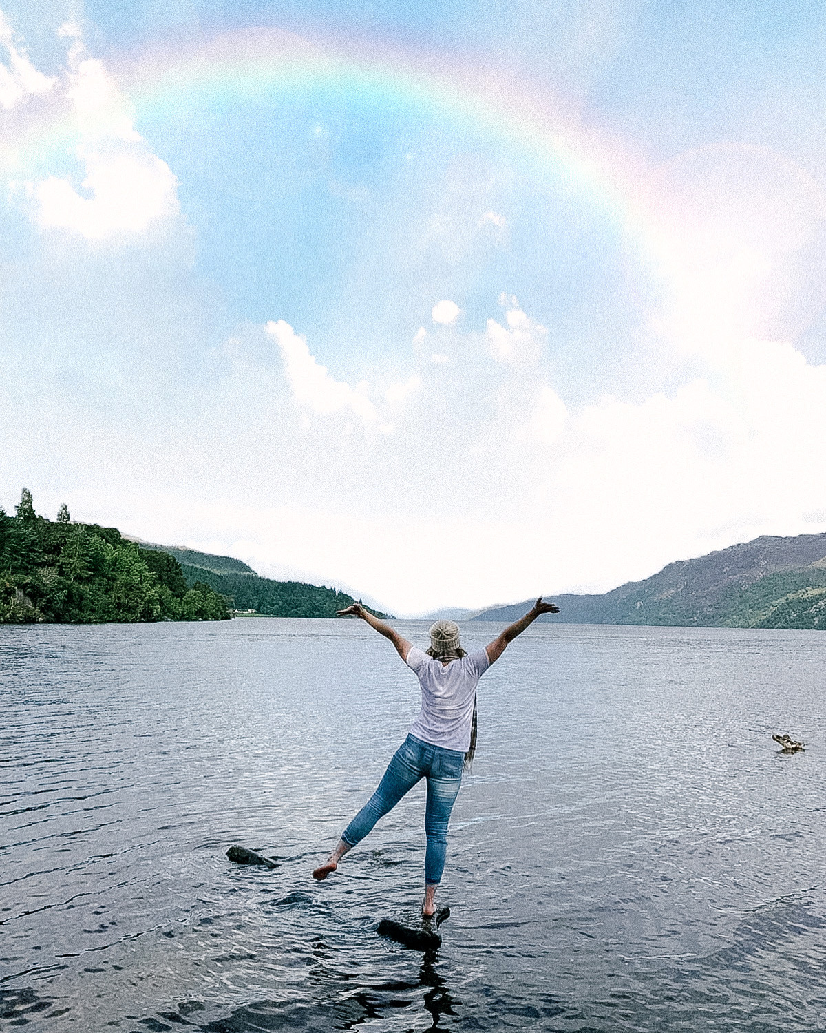 Travel blogger standing on the edge of Loch Ness in Scotland losing at a rainbow