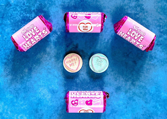 "4 mini rolls of love hearts in pink paper with 2 love hearts showing saying ""Marry Me?"" and ""Say Yes"""