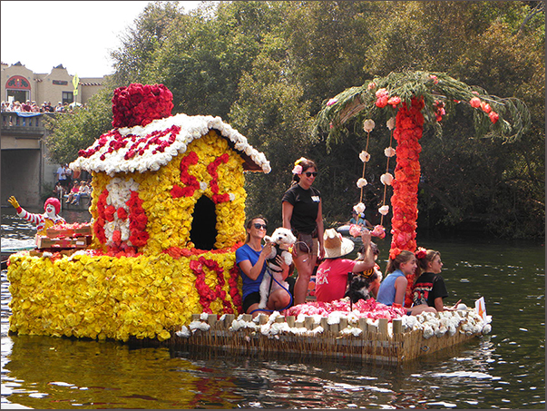 SPCA float with flower house and tree, 2 small dogs and several people
