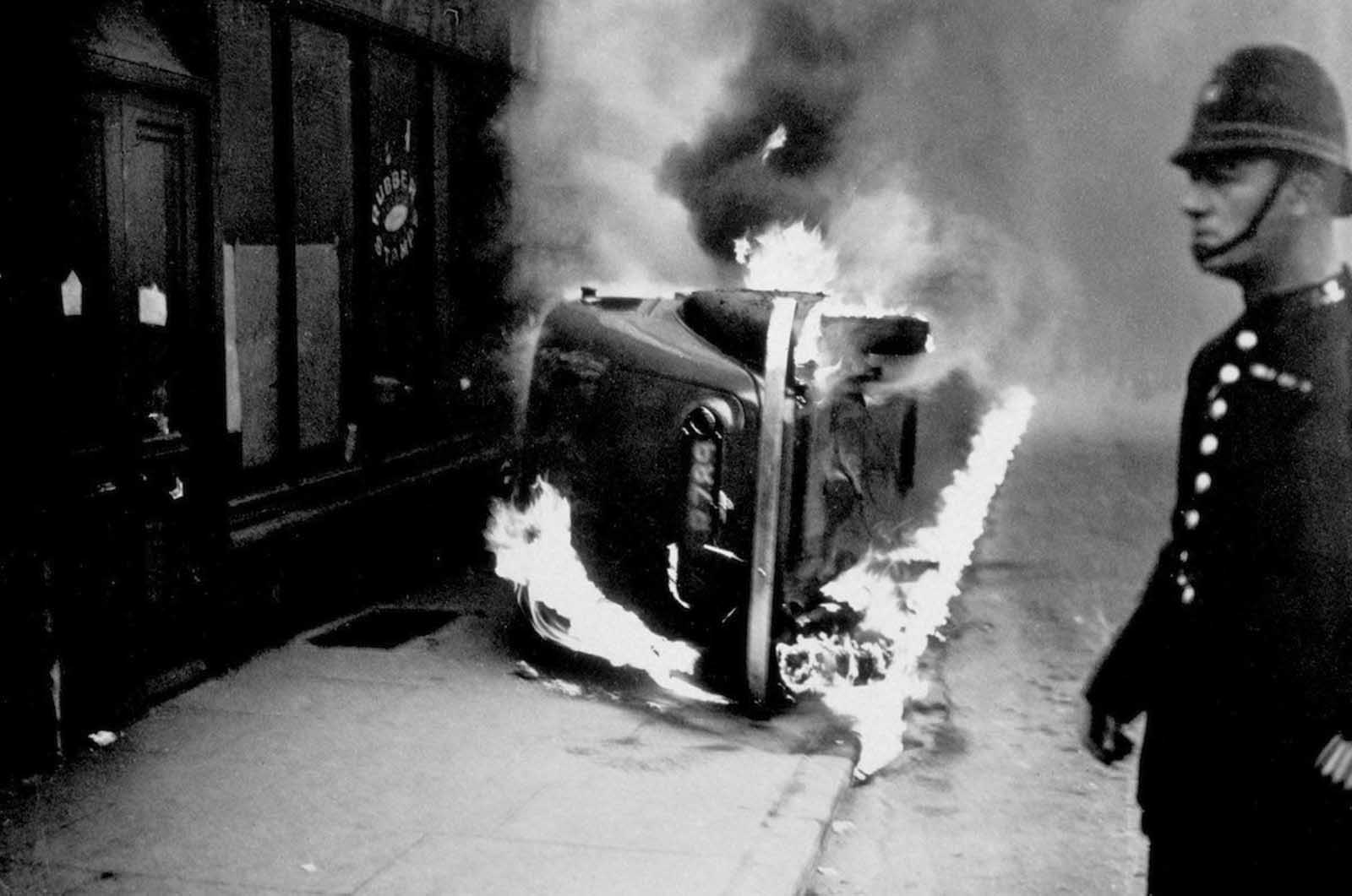 A policeman stands by a burning car, set alight during a communist march in the East End of London. 1936.