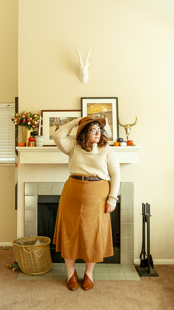 An outfit consisting of a brown panama hat, a cream cowl neck sweater half tucked into a brown A-line tea length skirt and a cognac d'orsay flats.