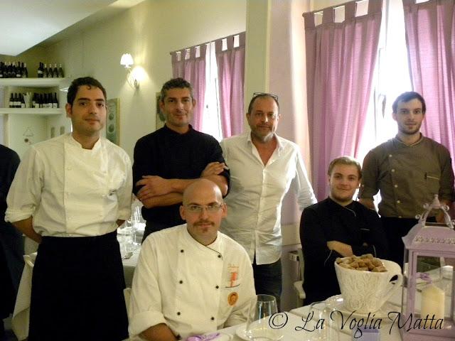 Luca Morgan in piedi con la camicia bianca e il suo staff