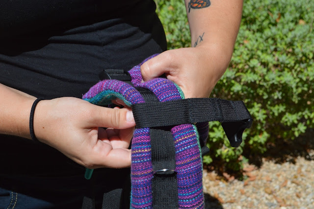 Image of fair skin woman adjusting the chest clip height on purple rainbow handwoven Onbuhimo strap