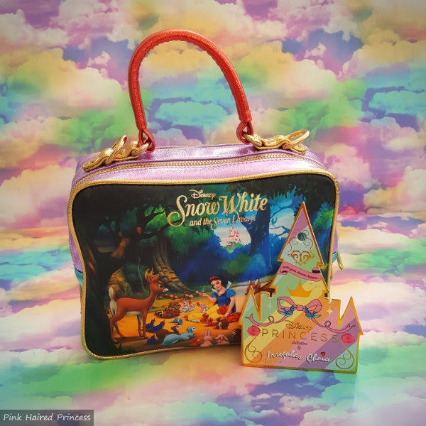 Snow White handbag with castle shaped tag on it on rainbow cloud background