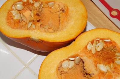 A picture of a pumpkin cut in half lengthwise, ready to be cooked to make pumpkin puree
