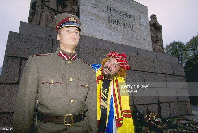 1996 год. Scotland fan John Grigor of Ayr meets a Latvian guard at the Freedom Statue in Riga