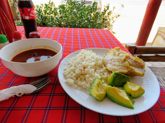 Plate of Ugandan food including beef, rice, matoke, and avocado
