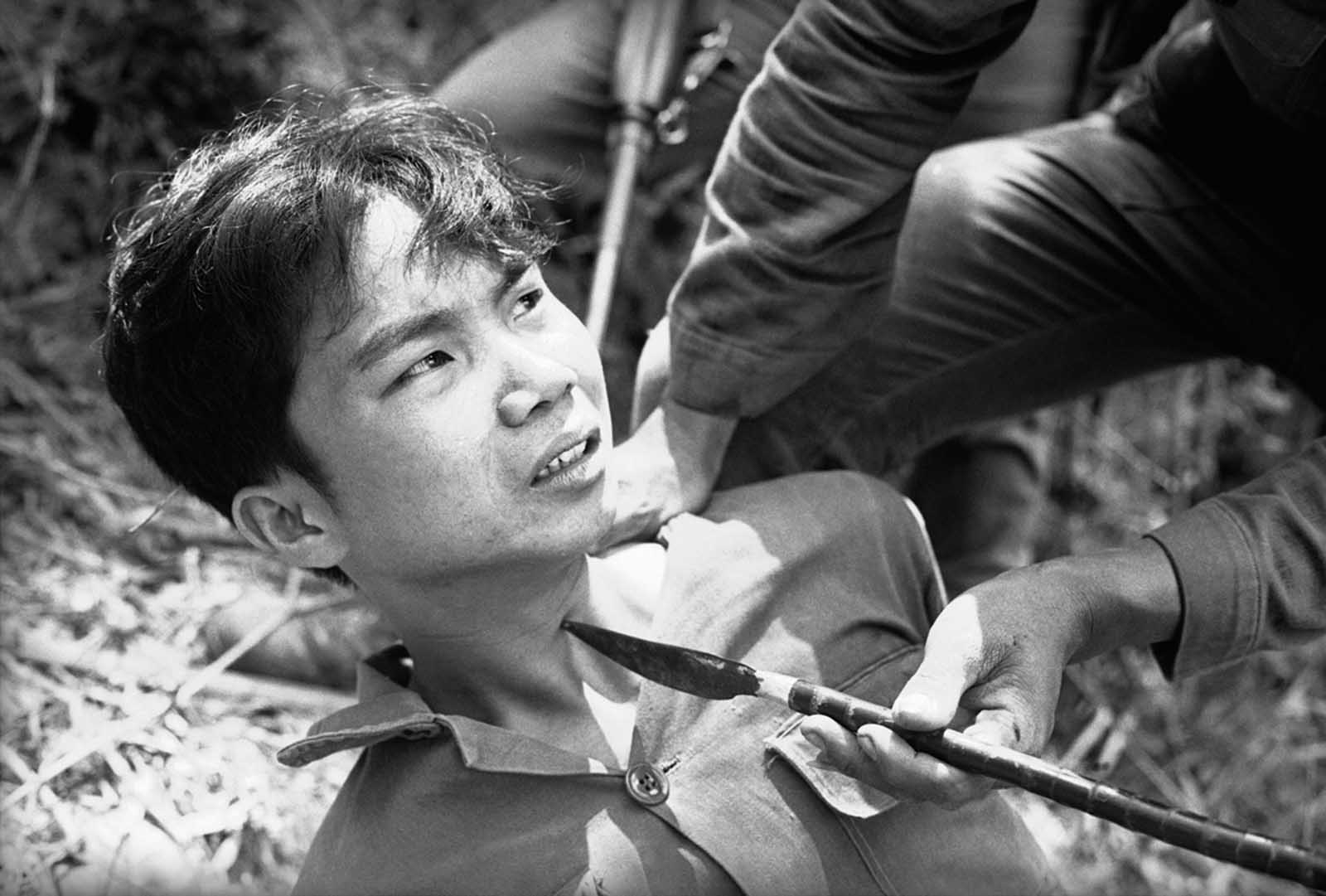 With the persuasion of a Viet Cong-made spear pressed against his throat, a captured Viet Cong guerrilla decided to talk to interrogators, telling them of a cache of Chinese grenades on March 28, 1965. He was captured with 13 other guerrillas and 17 suspects when two Vietnamese battalions overran a Viet Cong camp about 15 miles southwest of Da Nang air force base.