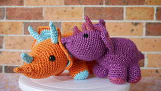 Two triceratops crochet plushies sitting on a cake spinner, one is larger (about 30cm from nose to tail) and made with orange cotton yarn. The other is much smaller, maybe 15cm from nose to tail, and is made with purple glittery acrylic yarn.