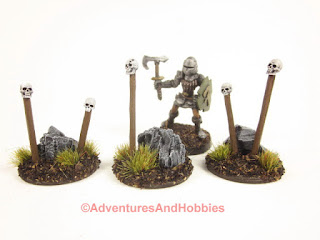 A 28mm fantasy warrior miniature stands among the skull totems.