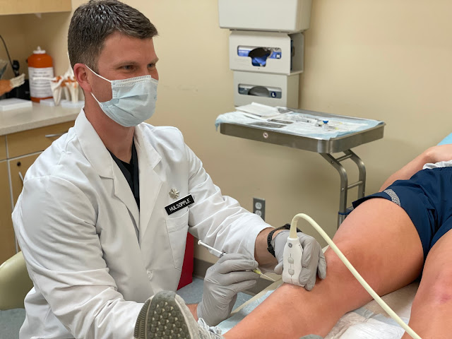 Dr. Hulsopple injects a patient with a syringe in the leg.