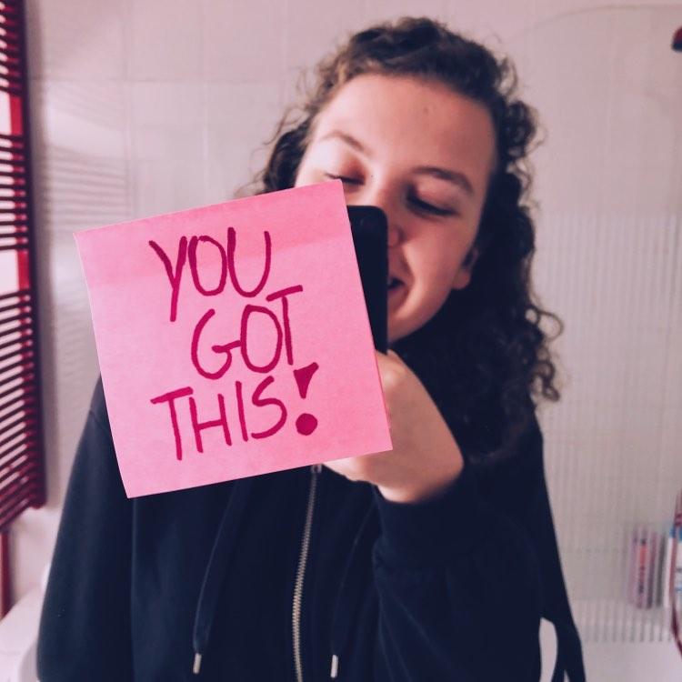 Spiegel selfie met een positieve boodschap: 'you got this', geschreven op een roze post-it op de voorgrond.