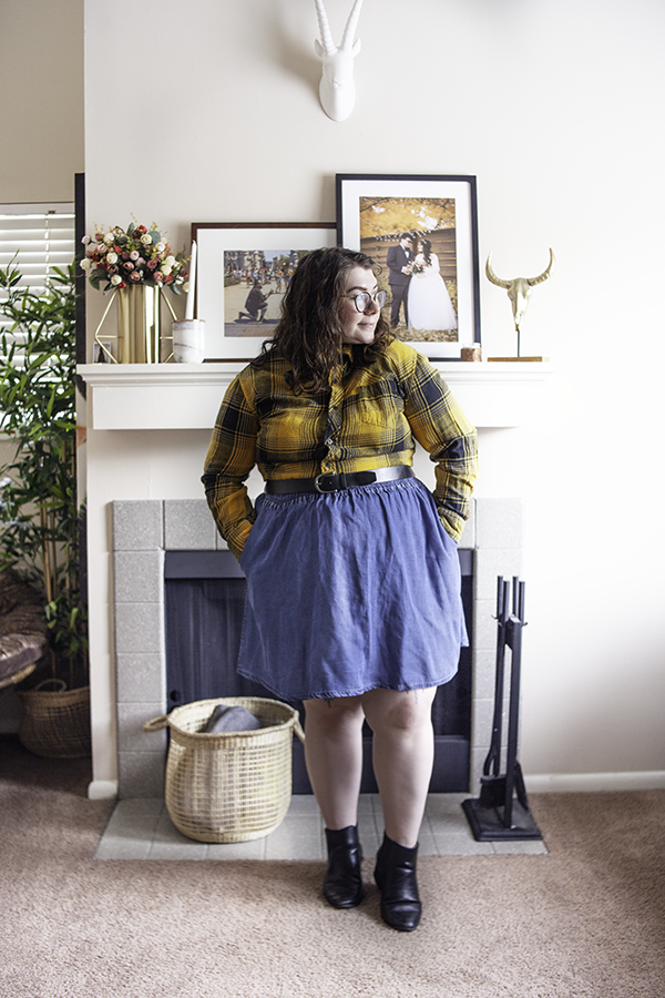 An outfit consisting of a black and yellow button down long sleeve flannel shirt tucked into a mini denim a-line skirt and black Chelsea boots.