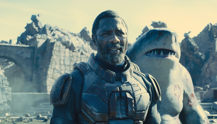 Imagem: o personagem Sanguinário, interpretado por Idris Elba, um homem negro com o cabelo curto e barba aparada, em um traje preto com detalhes metálicos azuis e cobre, por trás o Tubarão Rei, uma criatura humanóide com cabeça de tubarão e pele cinzenta e por trás várias ruínas de uma explosão recente.