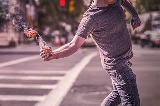 Participant à une émeute en train de jeter un cocktail Molotov