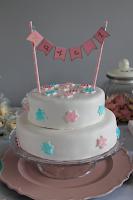 Witter stapeltaart met roze en turquoise sterren en vlaggenlijntje met naam