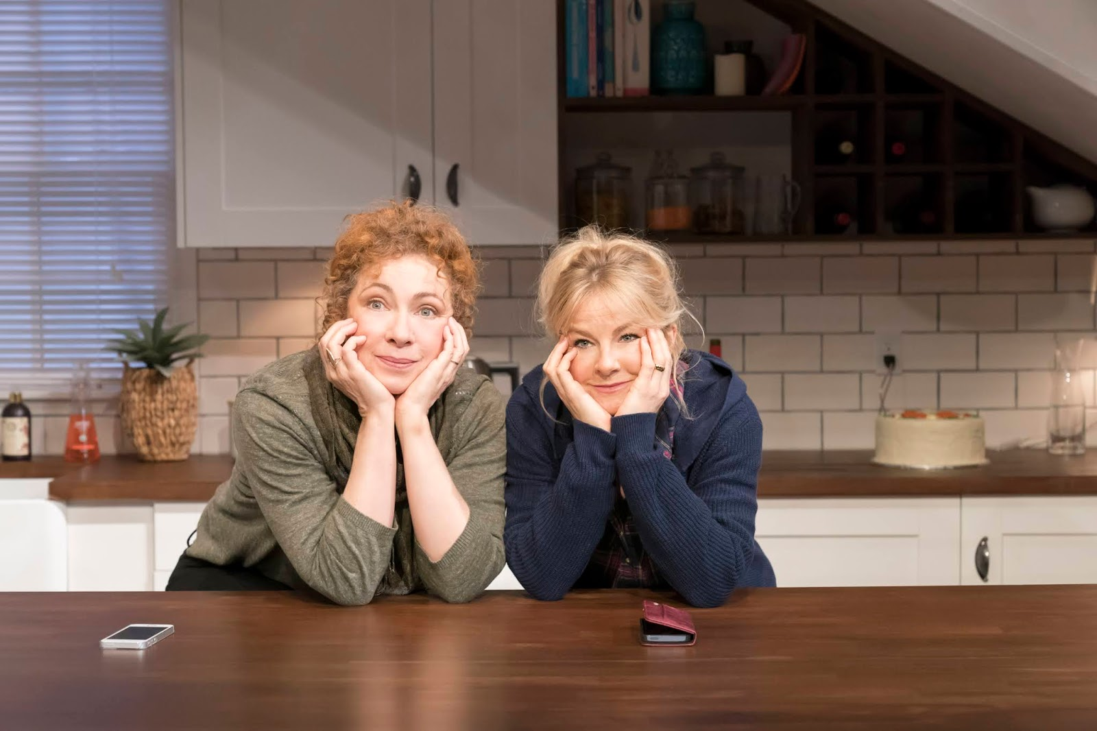 Actors in Admissions, Alex Kingston and Sarah Hadland, stand on-set, which looks like a kitchen