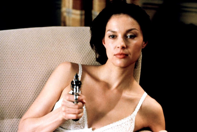 Ashley Judd points a gun at someone while trying to find the last Cheeto that she dropped on the floor