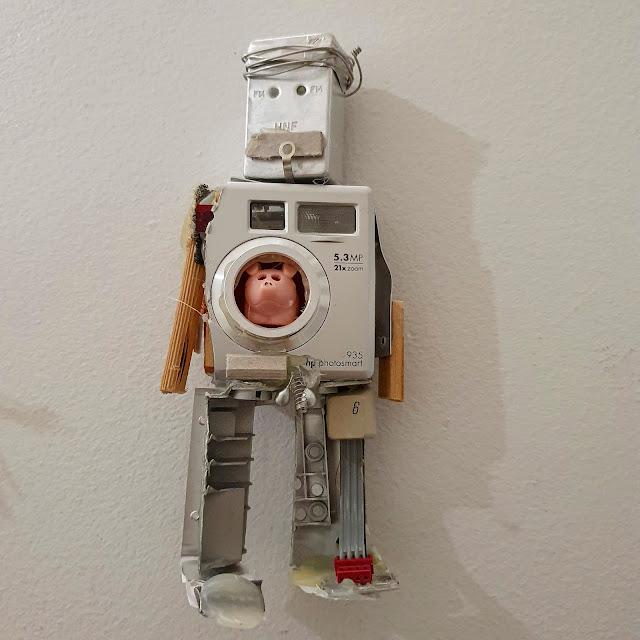 Kierrätysmateriaalista koottu humoristinen robottimainen hahmo. Sen torso on tehty vanhasta kamerasta, ja sulkimen aukosta kurkistaa muovista valmistettu porsas.