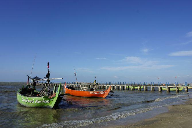 Perahu dan dermaga di pantai pasir putih Wates, Rembang