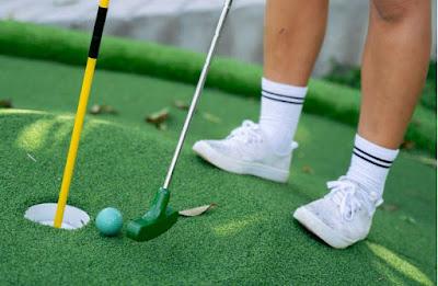 Närbild på green på bangolfbana med boll, hål och klubba