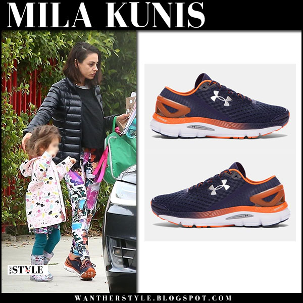 Mila Kunis in black puffer jacket and navy and orange sneakers under armour speedform casual style january 19
