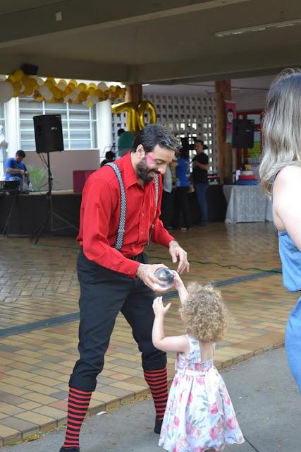 Malabarista de Humor e Circo interagindo com criança em evento do dia das crianças.