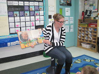 Adult reading book aloud to class
