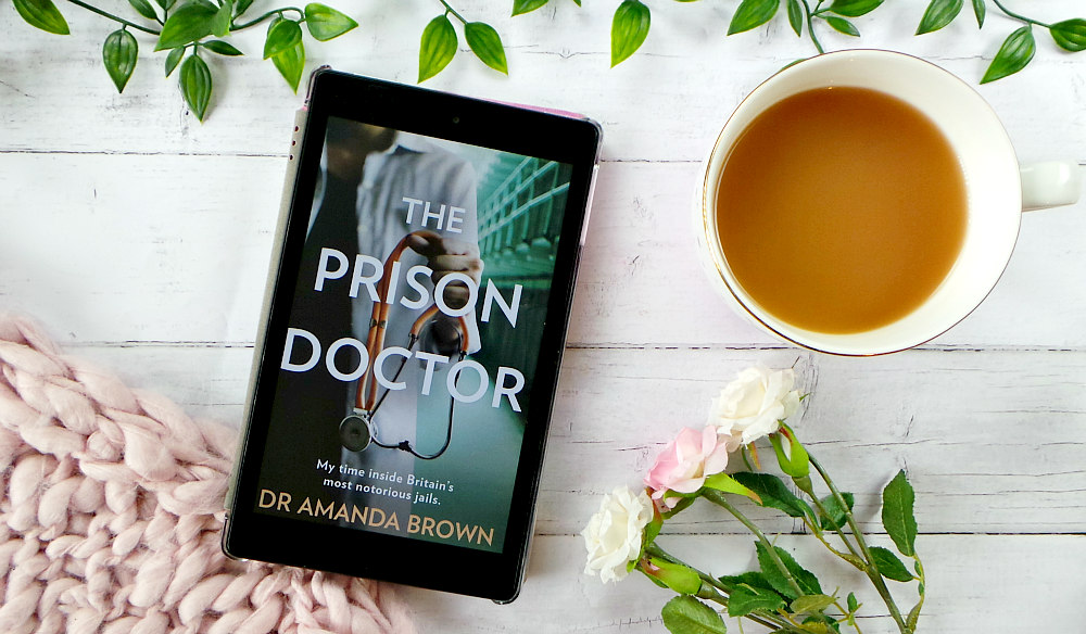 Kindle fire screen showing the cover for the prison doctor. The cover shows the torso of a woman wearing a white coat carrying a stethoscope. She is standing in the corridor of a prison. The background of the image features some leaves, roses, cup of tea and a pink chunky knit blanket