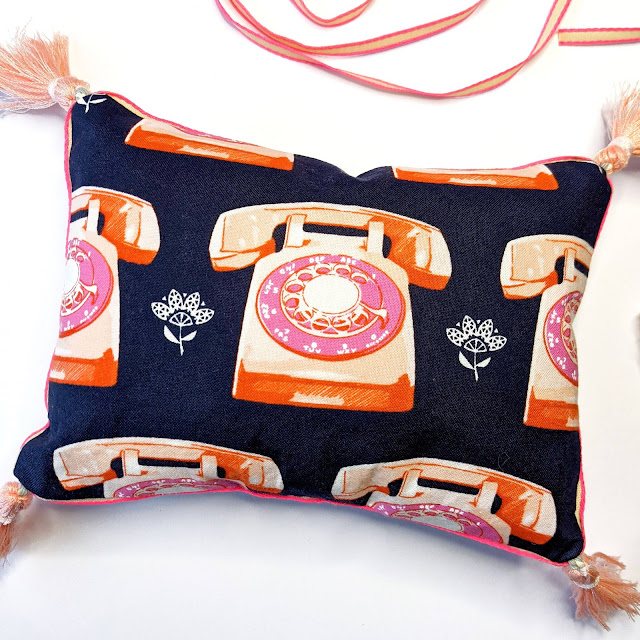 The back of the pillow with repeat 60s rotary telephone print fabric and corner tassels