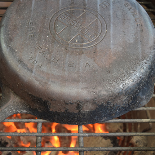 Using the Big Green Egg to strip a Griswold cast-iron skillet for restoration.