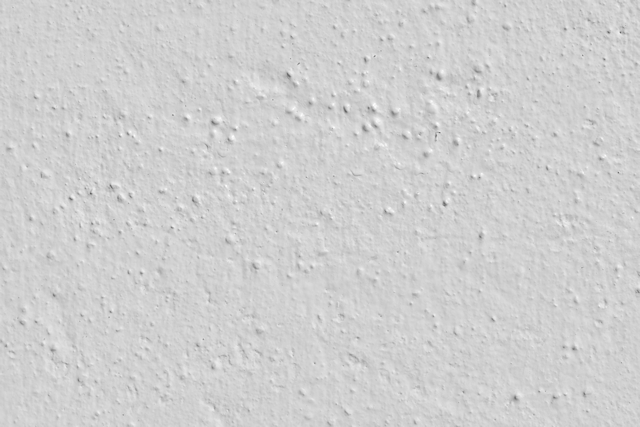White plaster wall with lumpy stucco