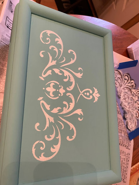 Photo of a turquoise jewelry box with a white ornate  scroll stencil