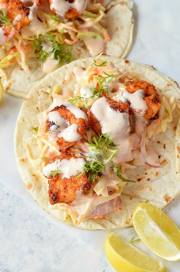 white background with spicy sriracha shrimp tacos with cilantro lime slaw