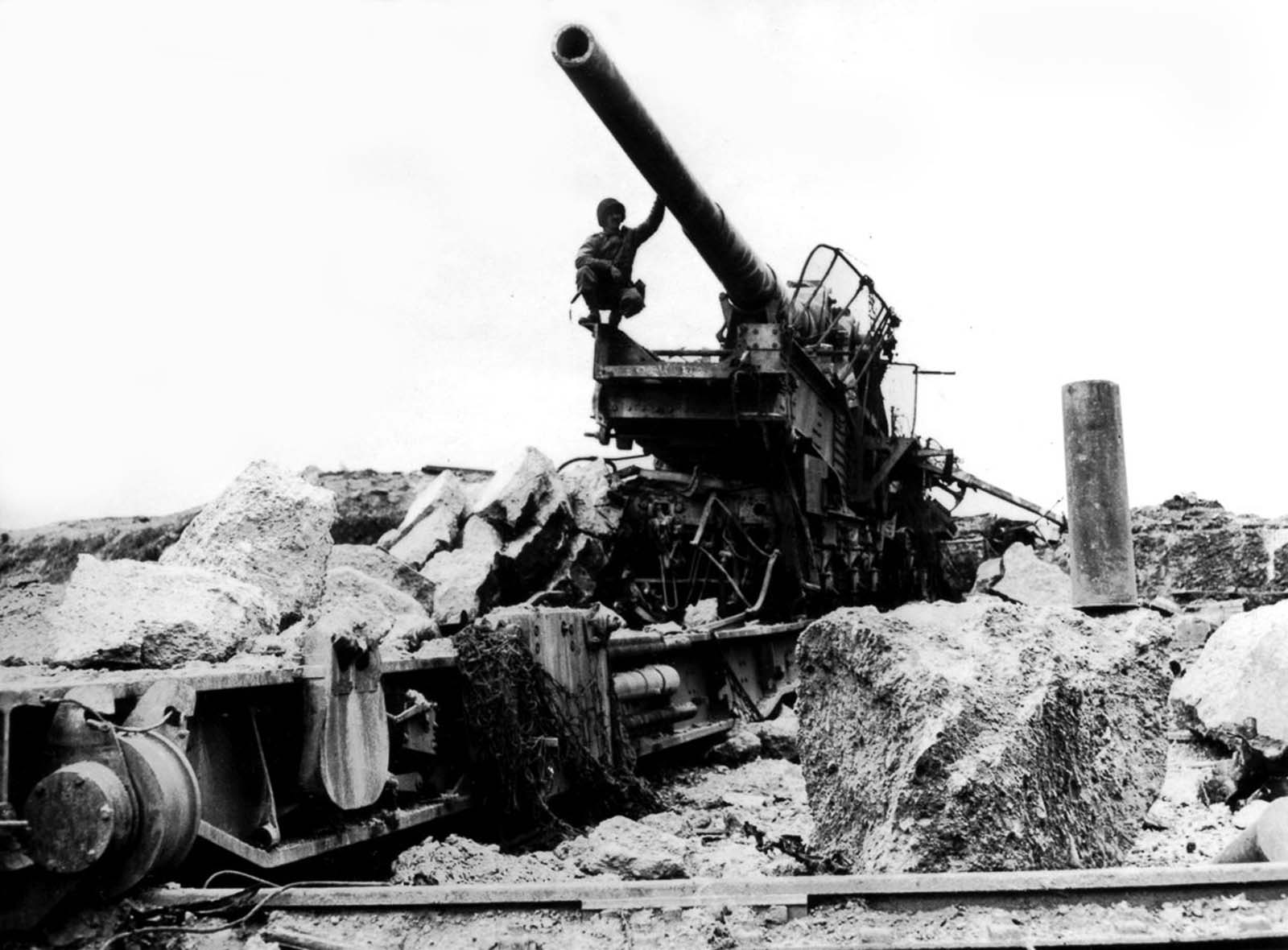 An American soldier examines a German 10-inch railway gun on the Cherbourg Peninsula in France. 1944.