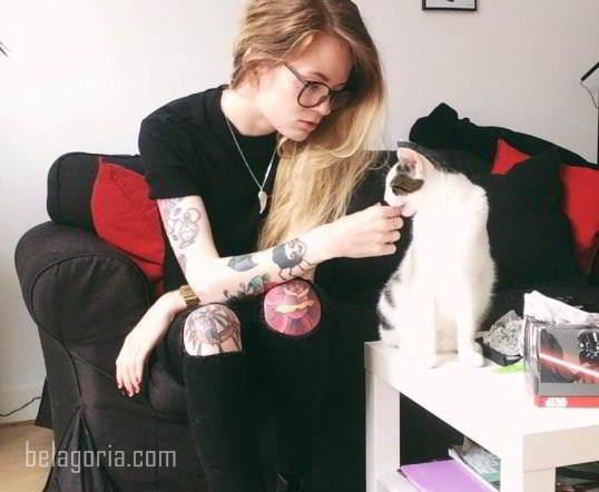 tatuaje en la rodilla de una preciosa joven que mima a un gato