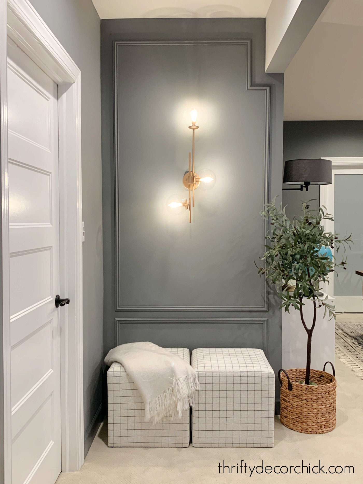 accent wall with box trim and brass sconce