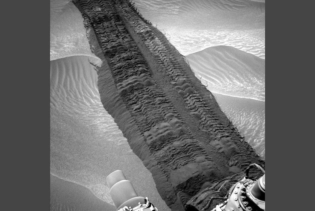 Hình ảnh này thấy rõ vết hằn bánh xe của tàu Curiosity được in dấu trên lớp cát khi nó chạy qua một vùng trũng có tên gọi là Thung lũng Hidden trên đường tiến tới Núi Sharp. Hình ảnh này được chụp vào ngày Sao Hỏa thứ 709, tức ở Trái Đất là ngày 4 tháng 8 năm 2014. Hình ảnh: JPL-Caltech/NASA.