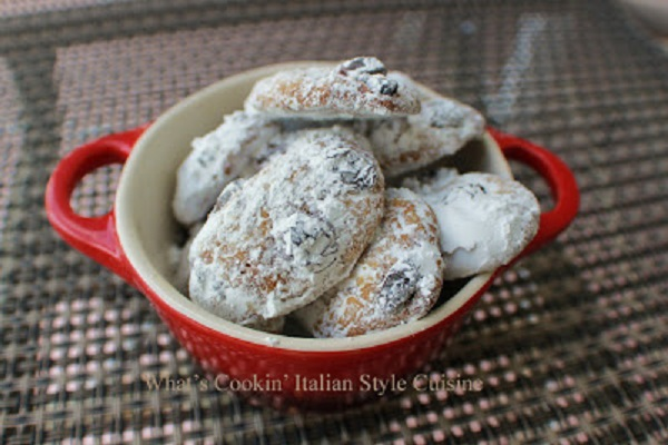 these are cookies in a red ceramic bowl for All Souls Day also All Saints Day cookies. The cookies are spiced and rolled in powdered sugar. This recipe is how to make traditional All Souls Day cookies.
