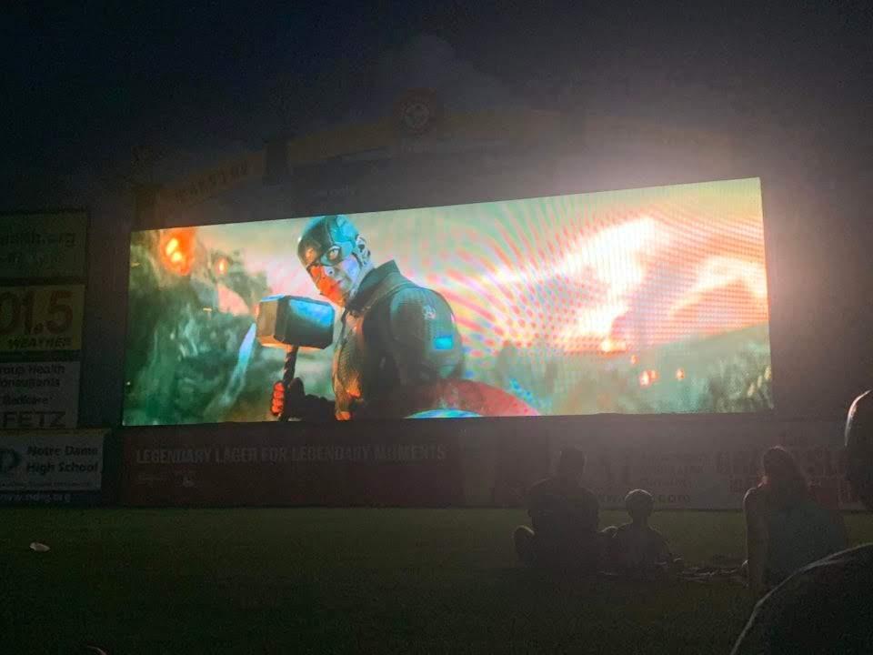 Avengers Endgame on the giant screen at a local minor league baseball field :  真夏の夜に野球場のグラウンドに座ったり寝そべったりの夕涼み気分で巨大スクリーンに映し出される「アベンジャーズ : エンドゲーム」を楽しむという最高にうらやましいイベントの写真 ! !