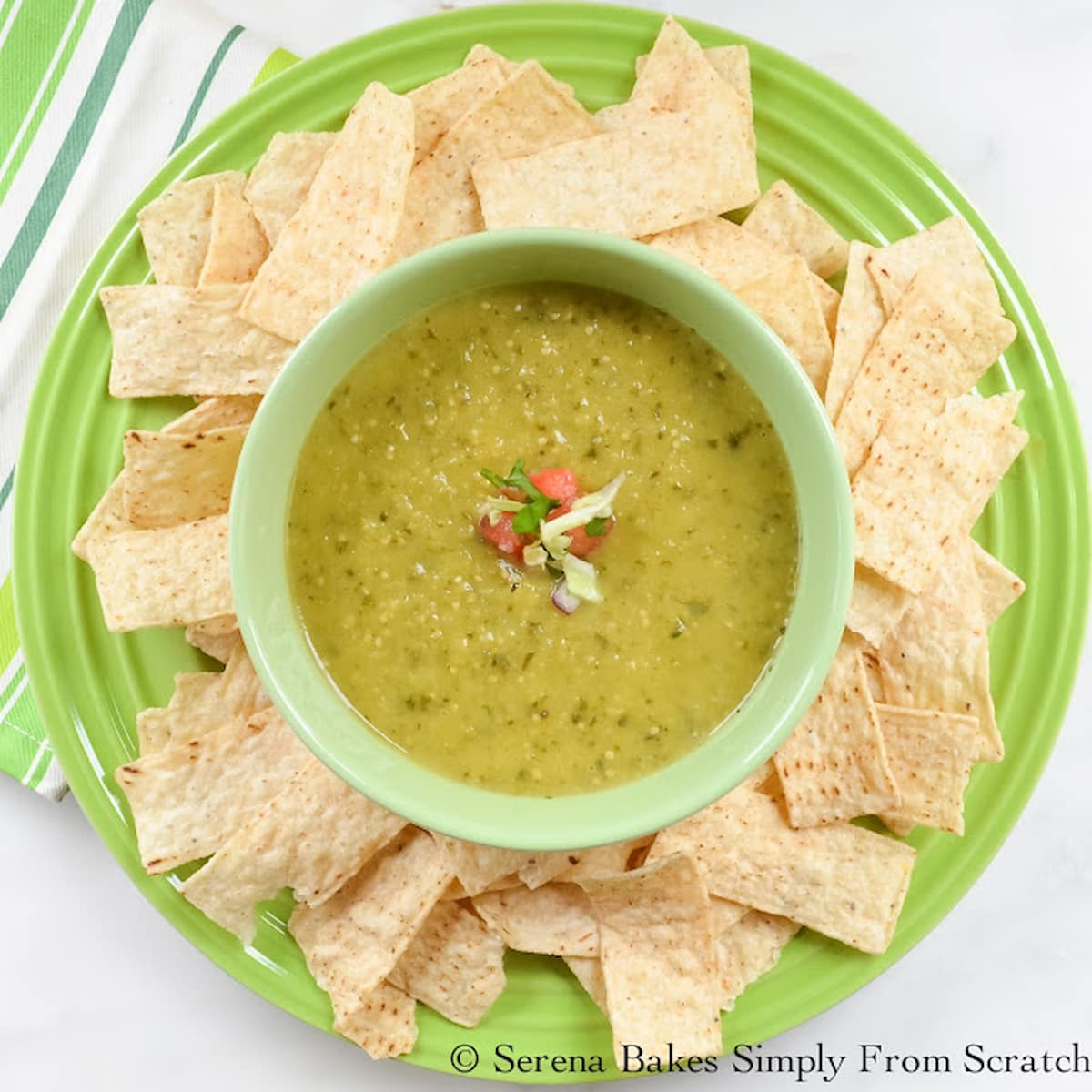 A green bowl filled with Salsa Verde and Corn Chips spread around the edge of a plate looking down.