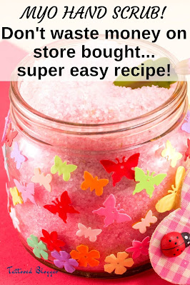 Homemade pink hand scrub in a small glass jar with paper butterflies on it
