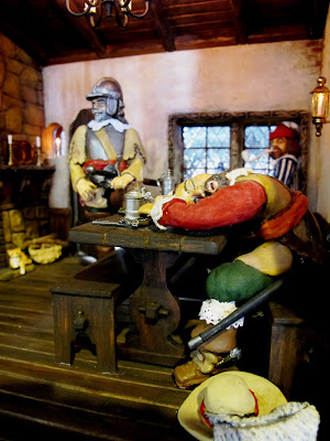 A man asleep at a table inside a one-twelfth scale miniature mid 17th-century inn.