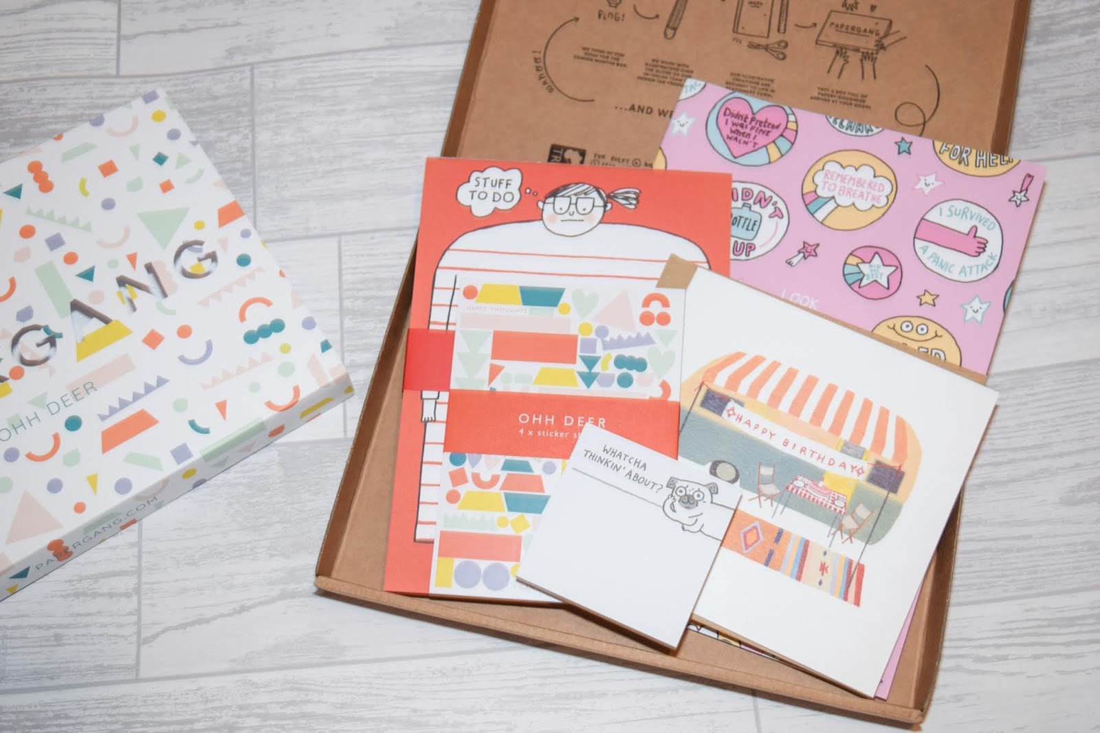 Overview contents of a mystery box of stationery including paper, stickers and a birthday card.