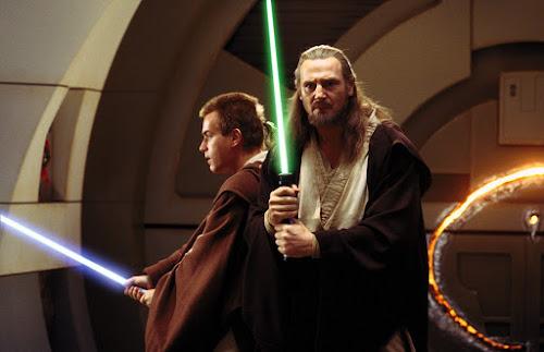 Obi-Wan Kenobi e Qui-Gon Jinn, interpretados por Ewan McGregor e Liam Neeson, empunhando seus sabres de luz, prontos para a luta