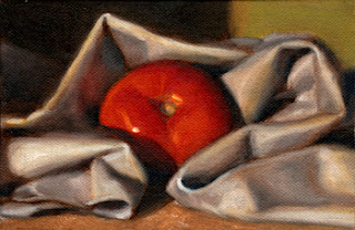 Oil painting of a red tomato partially wrapped in a tea towel.
