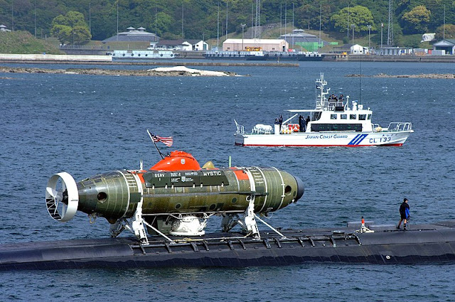 Image Attribute: The U.S. Navy Los Angeles-attack submarine USS La Jolla (SSN-701) with the deep submergence rescue vehicle Mystic (DSRV-1) attached, is escorted by the Japanese Coast Guard as it pulls out of Sasebo harbor to participate in the submarine rescue Exercise Pacific Reach 2002. / Source: U.S. Navy, Journalist 3rd Class Wes Eplen - This Image was released by the United States Navy with the ID 020425-N-0401E-003 (next).