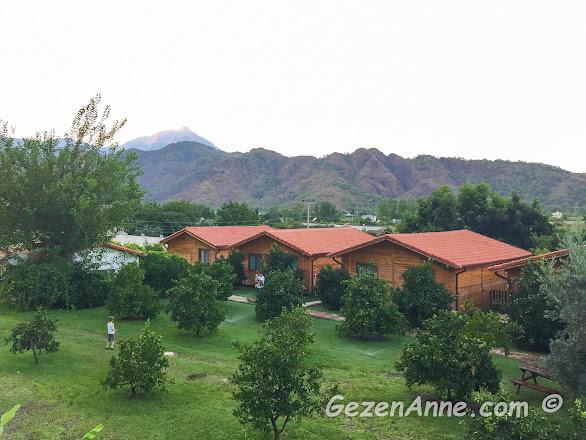 Azra Villas'ın yeşil bahçesi, arkada bir ucu Yanartaş olan Beydağları milli parkı, en arkada zirvesi 2365 metre olan Tahtalı dağı, Çıralı Antalya